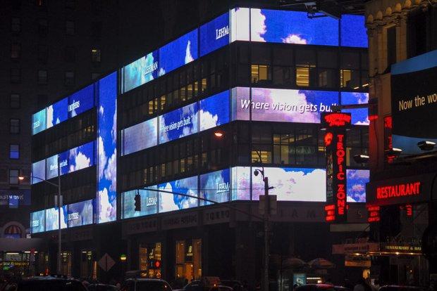 Ein großes Gebäude bei Nacht, an dem Leuchtreklamen entlanglaufen.
