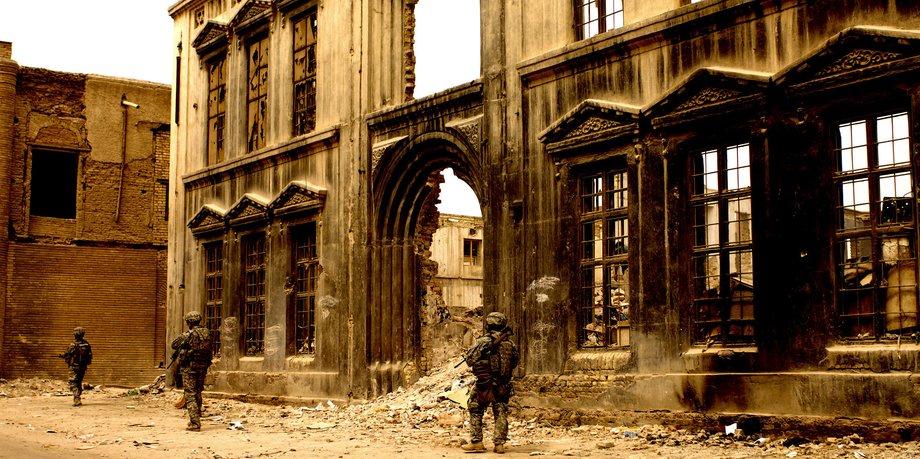 Eine Ruine eines Hauses, von dem nur die Frontseite noch steht. Davor gehen mit großem Abstand hintereinander drei Soldaten in Tarnuniform mit umgehängten Maschinengewehren.