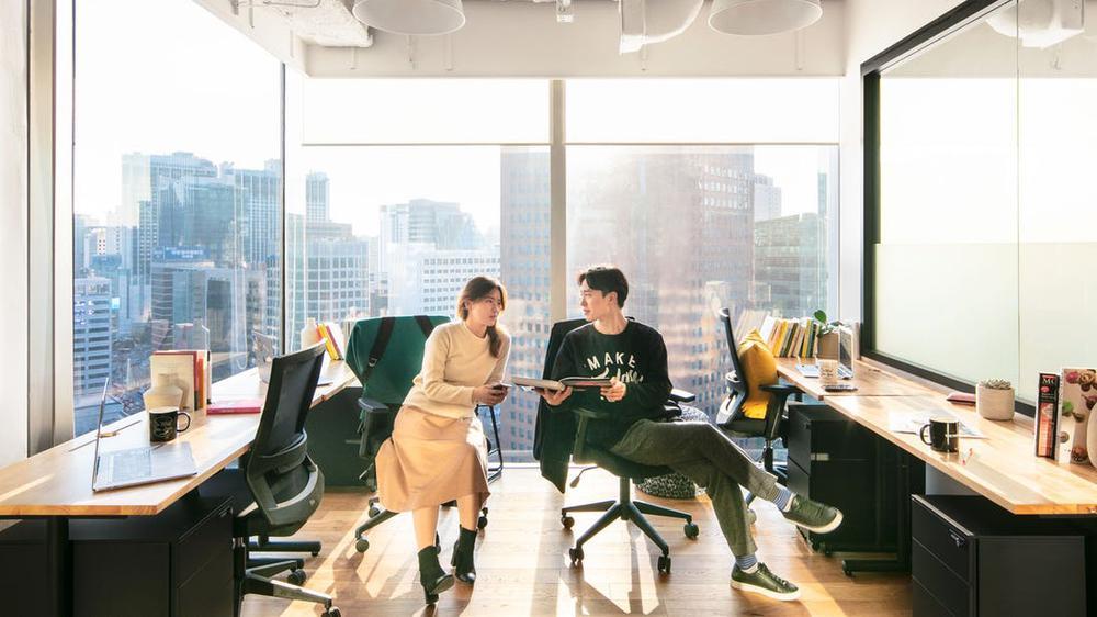 Büro mit Glasfenstern links und hinten, die vom Boden bis zur Decke reichen. Draußen ist die Silhouette einer Großstadt zu sehen. Drinnen stehen rechts und links je zwei Schreibtische