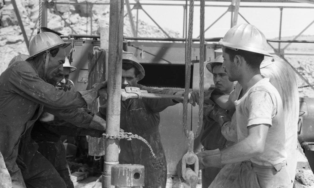 Schwarzweiß-Bild von iranischen Öl-Arbeitern, die eine Eisenrohrstange mit Zangen befestigen.