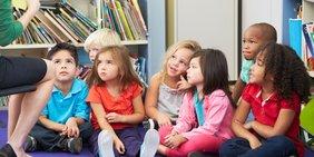 Kinder einer Kita oder Grundschule hören Lehrerin / Erzieherin zu