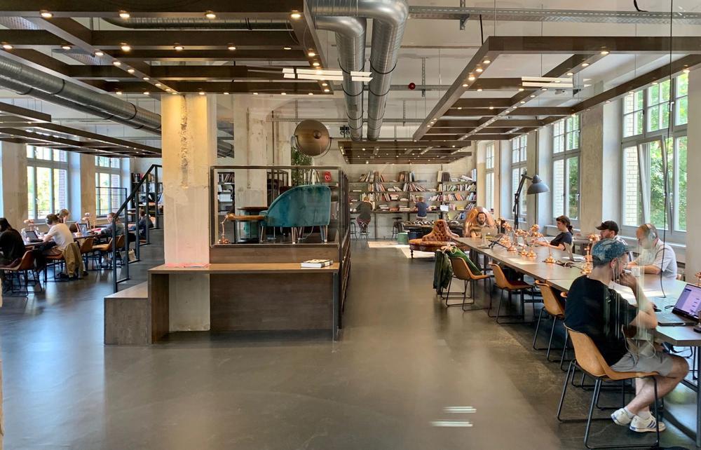 Modernes Büro mit langen Tischen rechts und links, jeweils entlang einer Fensterfront, mit Menschen, die an Labtops arbeiten.