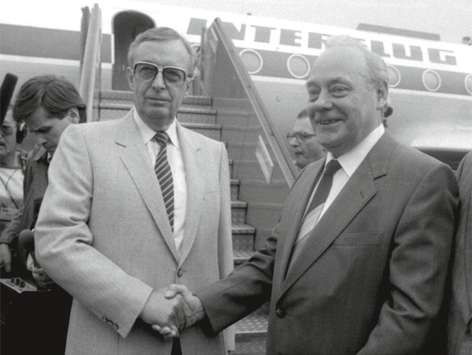 Ernst Breit und Harry Tisch stehen vor einem Interflug-Flugzeug und reichen sich die Hände.