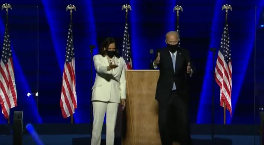 Kamala Harris und Joe Biden stehen auf einer Bühne, sie links, er rechts von einem Rednerpult, und winken ins Publikum. Beide tragen schwarze Gesichtsmasken.