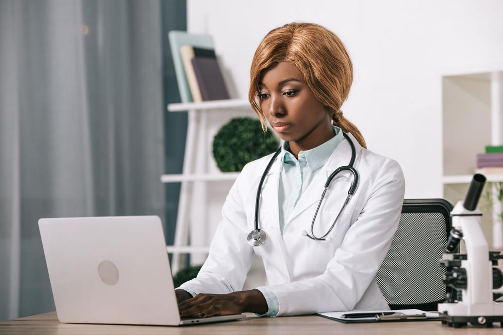 Ein dunkelhäutige Ärztin sitzt an einem Schreibtisch, Stetoskop umgehängt, und tippt in einen Laptop.