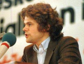 Olaf Scholz an einem Rednerpult, von halblinks aufgenommen, mit lockigem Haar