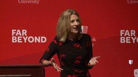 Stephanie Kelton hält einen Vortrag vor einer roten Wand mit dem Signum ihrer Universität. Sie trägt ein rotes Kleid und hat glatte, mittelange blonde Haare.