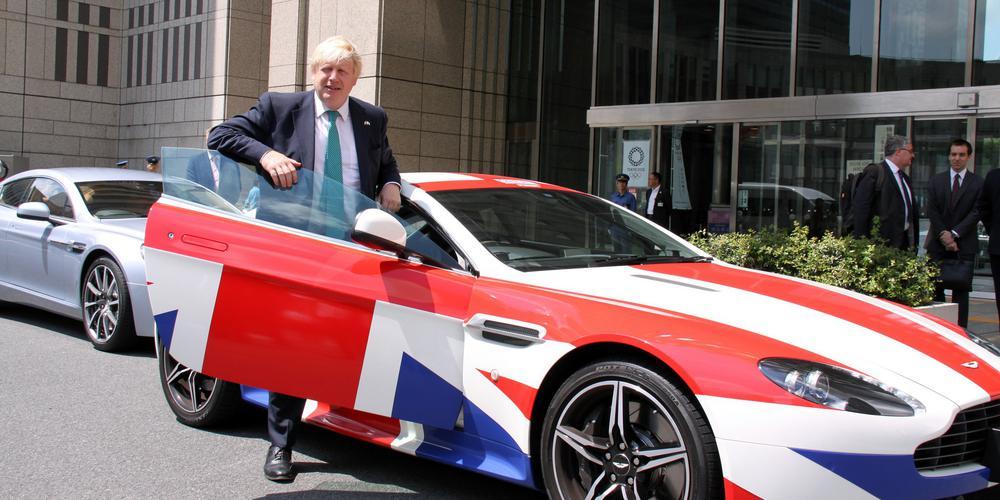 Boris Johnson steht bei geöffneter Tür vor einem Aston Martin der vollständig mit der britischen Flagge bemalt ist.