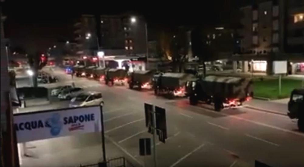 Ein Convoi von Militärlastern fährt nachts eine Straße in einer Stadt entlang.