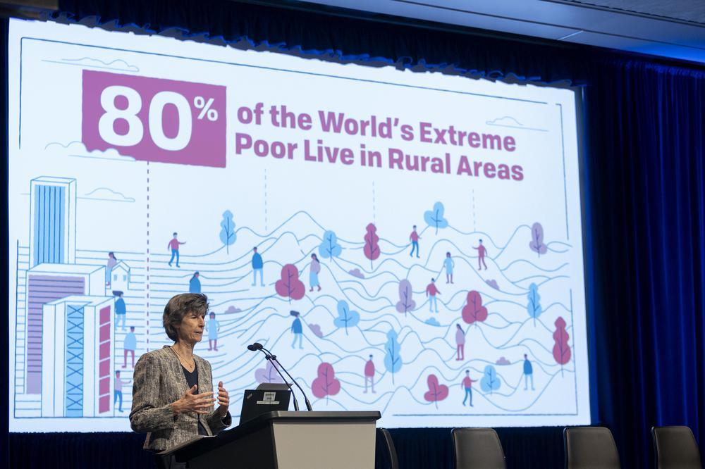 Eine Frau hält an einem Pult einen Vortrag, im Hintergrund ist auf Wand der Satz projeziert, dass 80 Prozent der Armen weltweit auf dem Land leben.