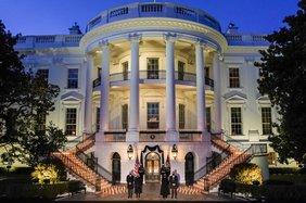 Das Weiße Haus in Washington in de Dämmerung mit Kerzen auf den Treppenstufen und Joe Biden und Kamala Harris.