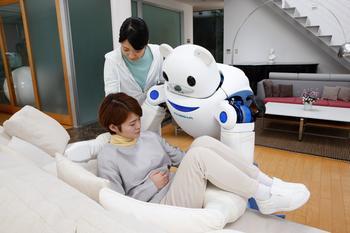 Ein Roboter hebt eine Frau von einem Sofa, im Hintergrund eine Pflegerin.