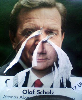 Wahlplakat, auf dem Scholz unten steht. Das Foto ist jedoch abgekratzt und dahinter kommt ein Plakat von Schröder zum Vorschein.