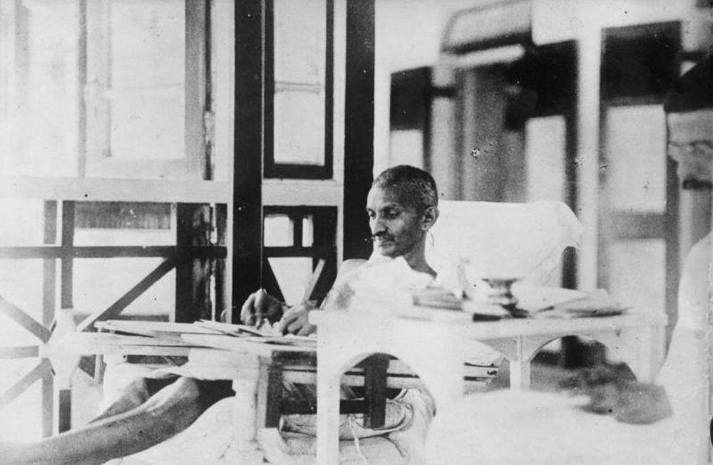 Mahatma Ganhi liegt auf einem Liegestuhl mit Tisch, auf dem er schreibt.