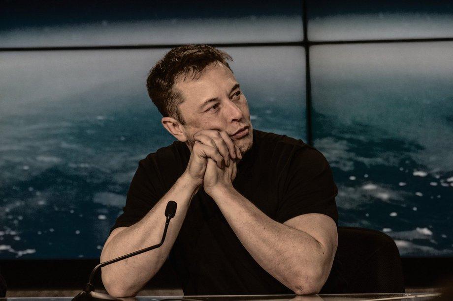 Elon Musk sitzt hinter einem Tisch, auf dem ein Mikophon steht. Im Hintergrund ist eine Aufnahme der Erde aus dem All an der Wand zu sehen. Er trägt ein schwarzes T-Shirt, aus dem sehr kräfitige Oberarme ragen, und blickt nach rechts.