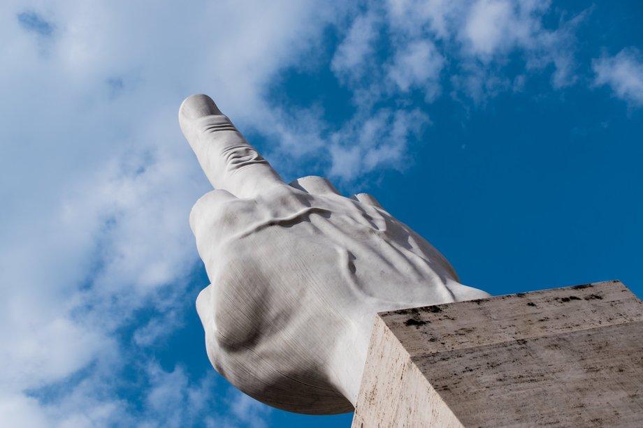 Die Statue zeigt einen großen marmornen Stinkefinger, der in einen blauen Himmel ragt.