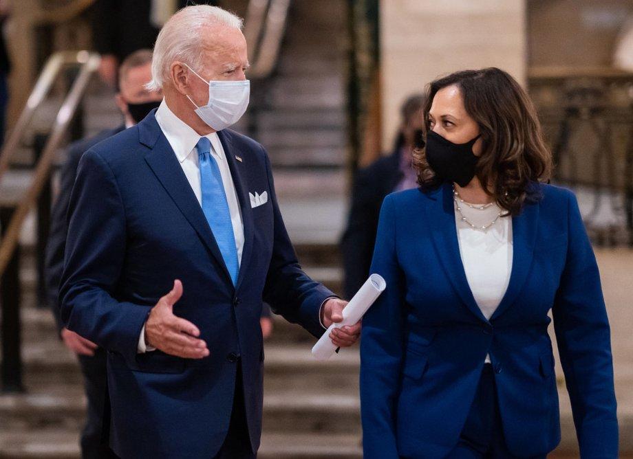 Joe Biden und Kamala Harris stehen nebeneinander, beide in blauen Anzügen, und sprechen miteinander. Sie tragen schwarze Gesichtsmasken.