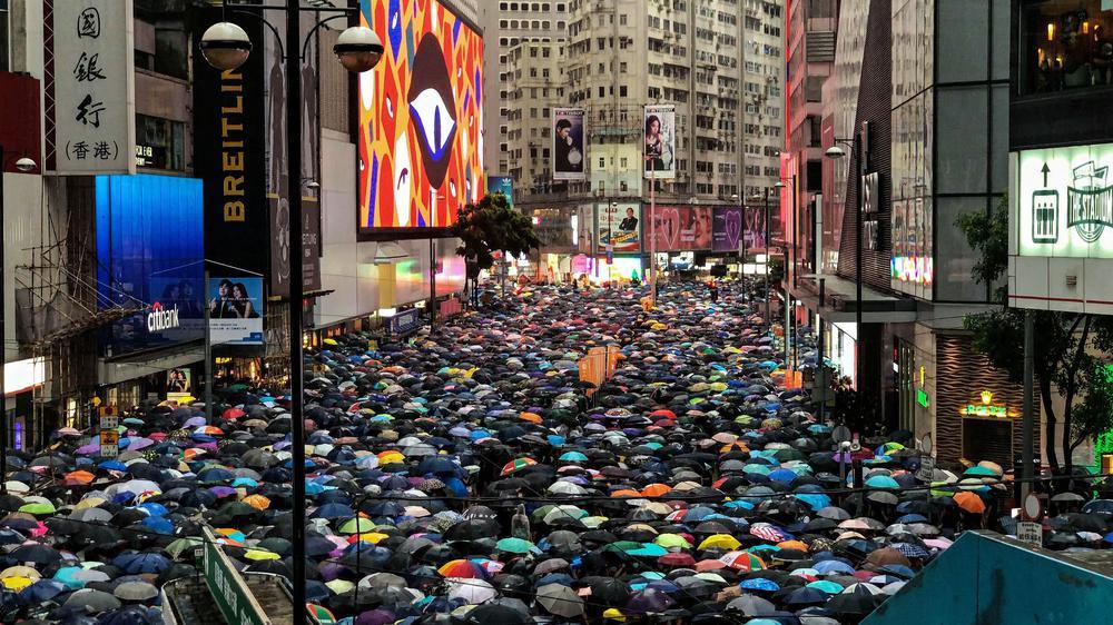 Tausende Menschen in einer langen Straße haben Regenschirme in allerlei Farben aufgespannt und protestieren so.