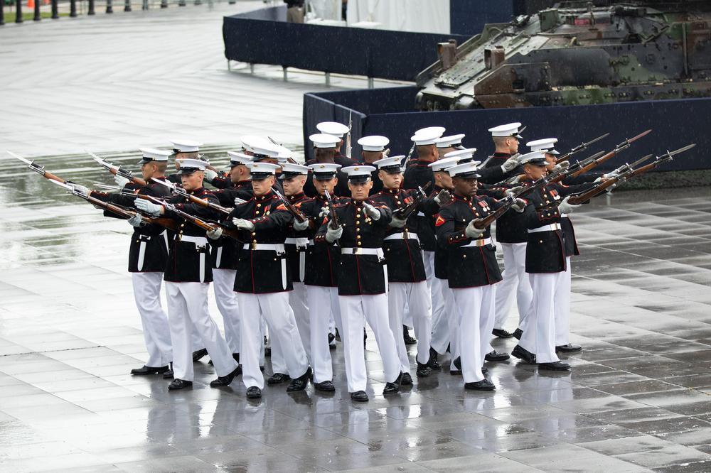 Soldaten eines US-Marine-Infanterie-Corps stehen in Formation und präsentieren ihrer Gewehre.