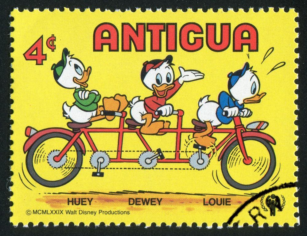 Briefmarke aus Antigua mit einer Zeichnung von Tick, Trick und Track auf einem Tridem-Fahrrad, darunter ihre englischen Namen Huey, Dewey, and Louie.