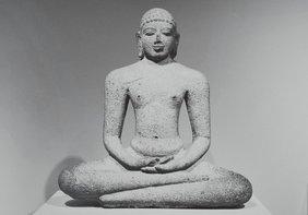 Eine steinerne Skulptur eines meditierenden Mannes.