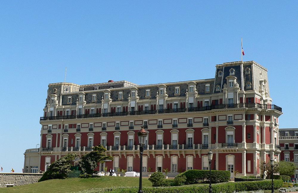 Großes Haus im Belle-Epoque-Stil. Es hat eine rote Fassade mit weißen Halbsäulen zur Gliederung der Fassade.
