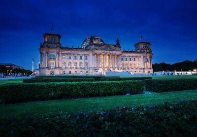 Reichtstagsgebäude in Berlin vor nachtblauem Himmel.