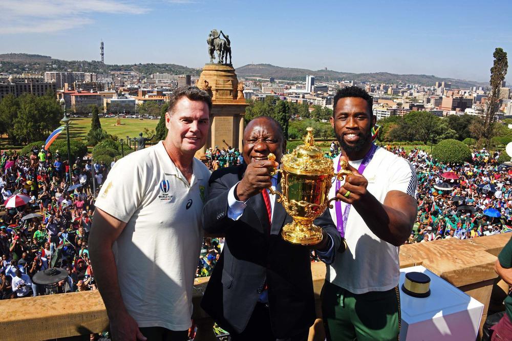 Der Rugby-Spieler Siya Kolisi steht mit Südafrikas Präsident Cyril Ramaphosa und seinem Trainer Rassie Erasmus auf einem Balkon vor vielen Menschen und hält den WM-Pokal in die Höhe.
