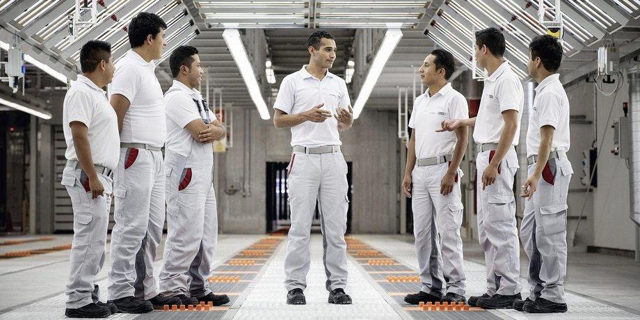 Arbeiter in heller Funktionskleidung stehen in einem Tunnel aus Neonröhren.