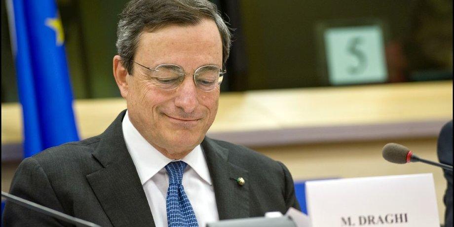 Mario Draghi sitzt hinter einem Tisch mit Mikrophon und lächelt mit leicht gesenktem Blick.