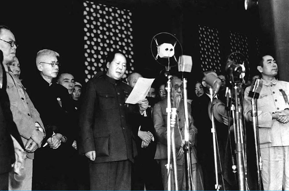 Historisches Schwarzweiß-Bild mit Mao Tse-tung, der in auf einer Bühne in eine Mikrofon spricht. Neben und hinter ihm stehen lauter uniformierte Männer.