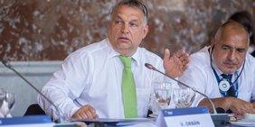 Viktor Orbán spricht an einem Tisch hemdsärmelig sitzend in ein Mikrofon.