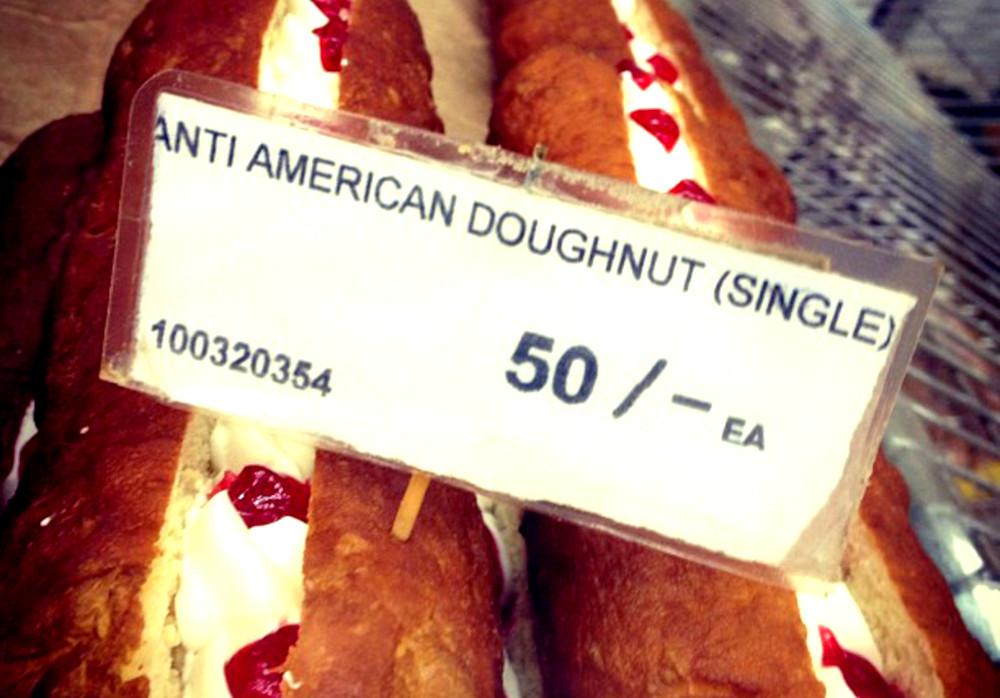 Ein Donut liegt in einer Auslage. Darüber steht ein Schild mit der Aufschrift: Anti American Doughnut.
