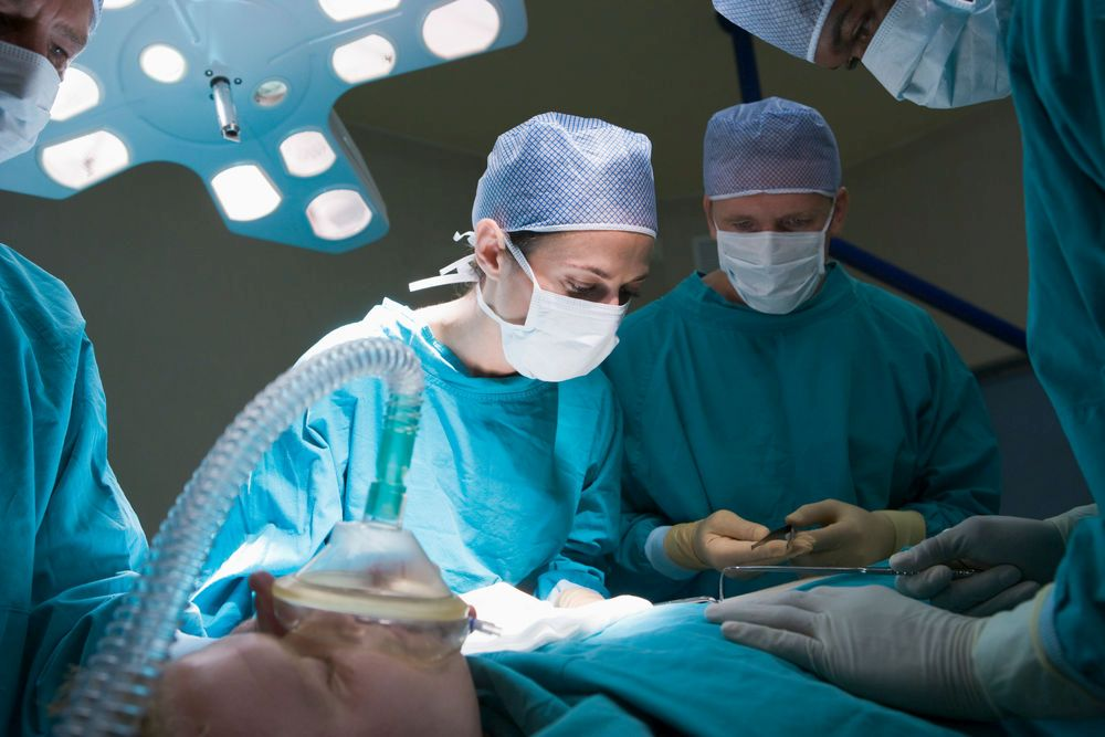 Mehrere Ärzte in blauen Kitteln mit OP-Masken stehen um einen Operationstisch, auf dem ein Patient liegt.