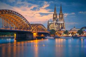 Silhouette der Stadt Köln mit Dom und stählerner Eisenbahnbrücke bei Morgengrauen.
