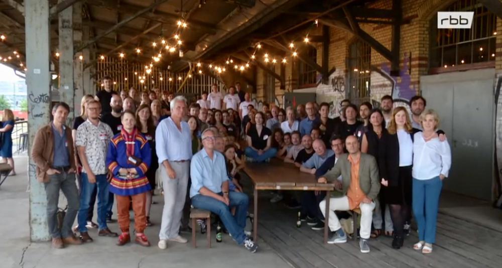 Versammelt um einen großen Tisch, teils sitzend, teils dahinter stehend sind 60 Menschen unterschiedlicher europäischer Nationalitäten zu sehen.