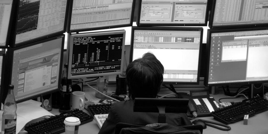 Ein Mann sitzt vor etlichen Computerbildschirmen und Telefonen in der Börse Frankfurt.