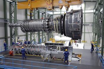 Eine riesige Gasturbine hängt an Stahlseilen in einer Werkshalle