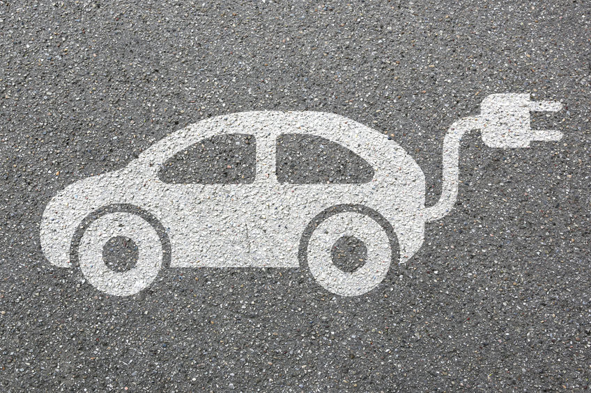 Symbolische Darstelleung eines Autos mit Kabel und Stecker, auf Asphalt gemalt.