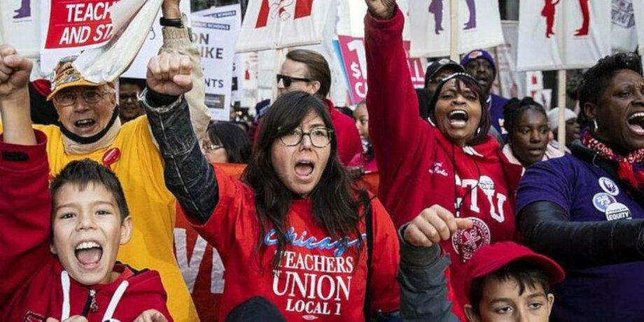 Lehrerinnen und Lehrer protestieren mit Schülern, alle mit erhobenen Fäusten.