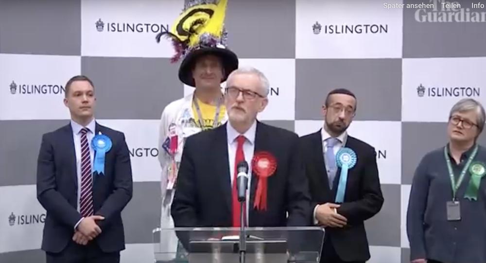 Jeremy Corbyn steht hinter einem Rednerpult. Hinter rechts und links stehen zwei Männer und eine Frau, die alle recht traurig blicken.