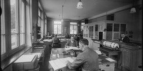 Angestellte in Arbeitskitteln sitzen an Schreibtischen, auf denen Rechenmaschinen, Stempelhalter mit Stempeln und Stifte stehen. Das Bild ist in schwarzweiß.