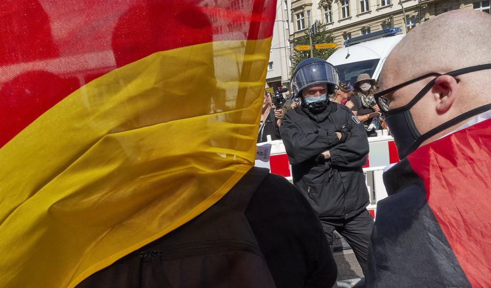 Demonstranten, die eine Deutschlandfahne tragen, sind von hinten zu sehen, vor ihnen steht ein Polizist, der Kamera zugewandt, mit Helm.