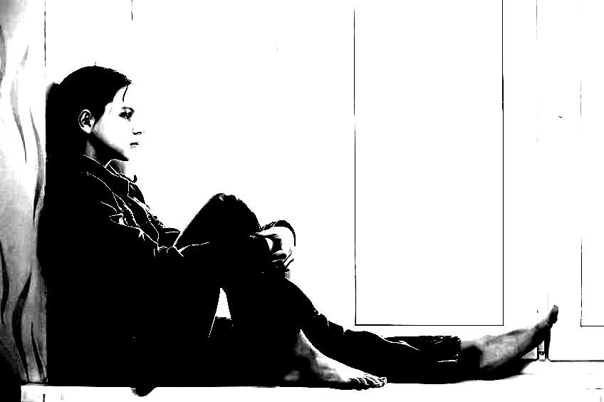 Ein Kind sitzt auf einer Fensterbank. Bild ist kontrastreich in Schwarzweiß.