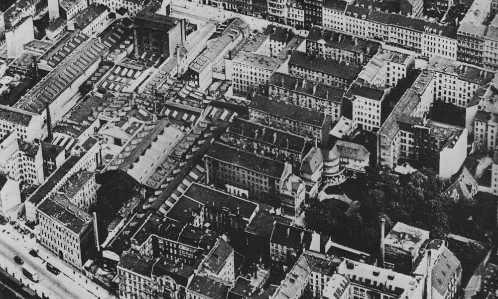 """Blick von oben auf die berühmten Mietskasersen """"Meyer's Hof"""" mit Vorderhaus und fünf Hinterhäusern; alles sehr eng bebaut, daneben eine Fabrikanlange."""
