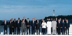Die Teilnehmer des G7-Gipfels stehen aufgereiht zum Gruppenbild in Biarritz, im Hintergrund ein Abendhimmel mit Leuchturm halblinks.