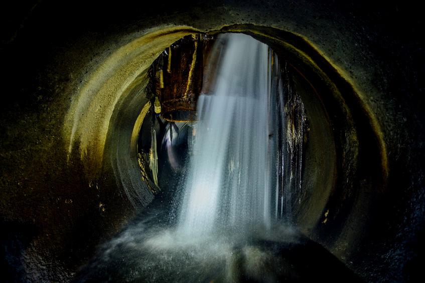Wasser stürzt von oben in einen Abwasserkanal.