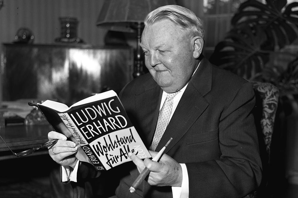 """Ludwig Erhard sitzt in einem Sessel und blickt in das Buch """"Wohlstand für alle""""."""