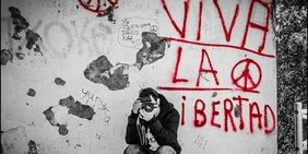 Ein Fotograf kniet vor einer Hauswand, auf der in roten Buchstaben gemalt ist: Viva la Libertad.
