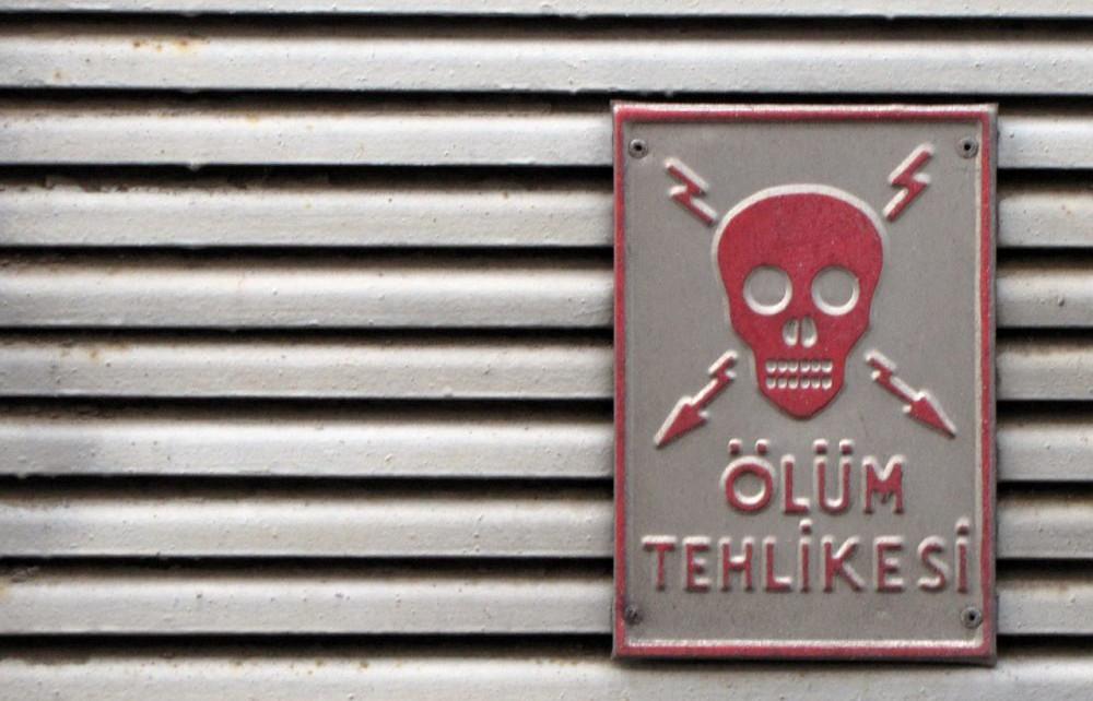 Stromkasten mit einem Schild, auf dem ein Totenkopf prangt und in Türkisch steht: Lebensgefahr.